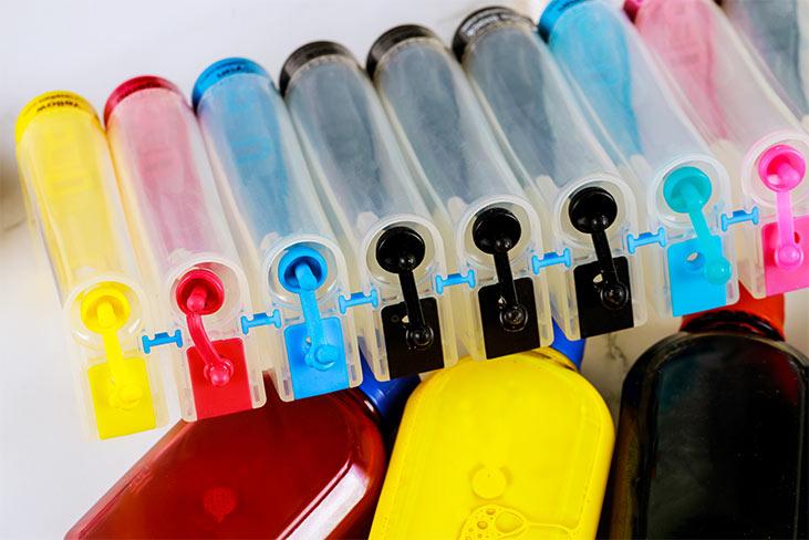 مخازن جوهر متصل به بطری هایی با رنگ های مختلف در یک ردیف_ عکس استفاده شده در سایت aloocartridge.com