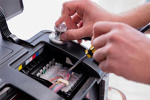 تعمیرکار در حال تعمیر یک پرینتر رنگی معیوب_ عکس استفاده شده در سایت aloocartridge.com